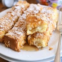 crunchy baked french toast sticks on white plate with powdered sugar and syrup