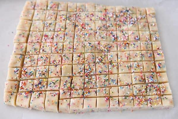 cutting funfetti shortbread bites into tiny squares