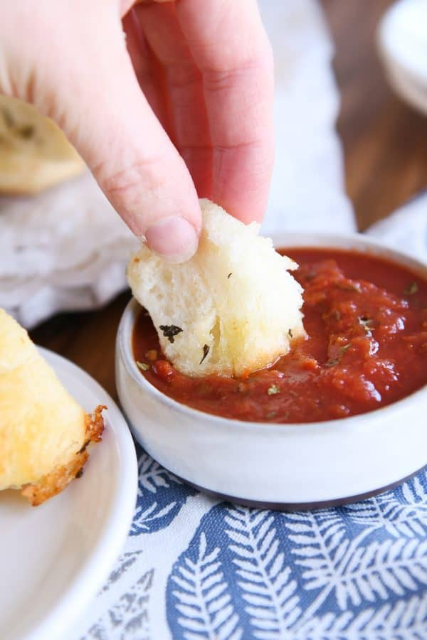 dipping piece of pull-apart bubble bread in marinara sauce