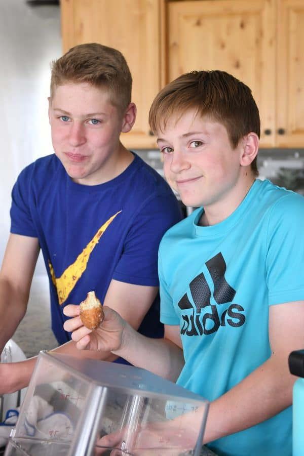 two teenage boys testing the best homemade glazed donuts recipe