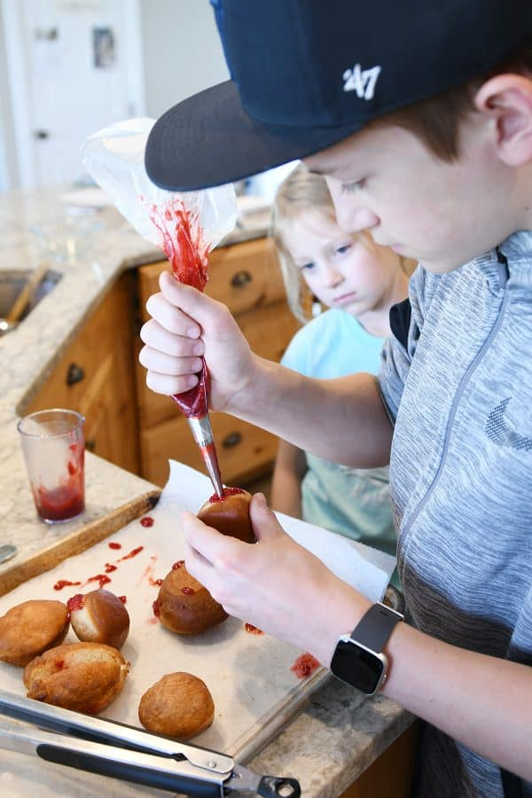 piping raspberry jam into homemade donuts