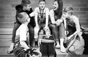 mom sitting in bleachers talking to her kids