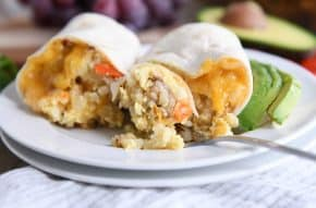 easy freezer breakfast burrito cut in half with bite on fork on white plate