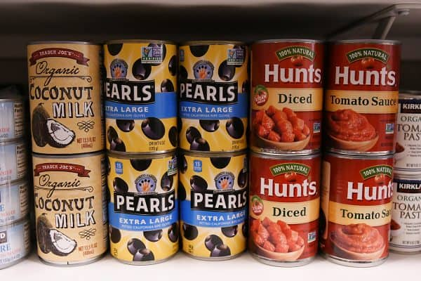 olives and coconut milk and diced tomatoes on pantry shelf