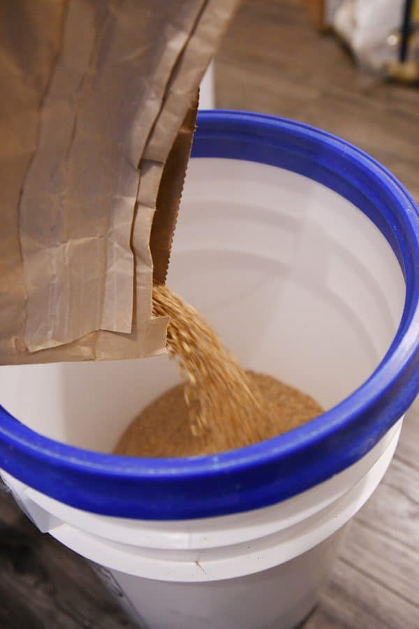 pouring wheat from brown bag into 5 gallon bucket