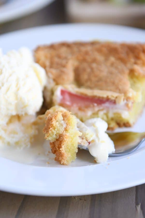 piece of rhubarb custard cake on white plate with ice cream and fork taking out a bite