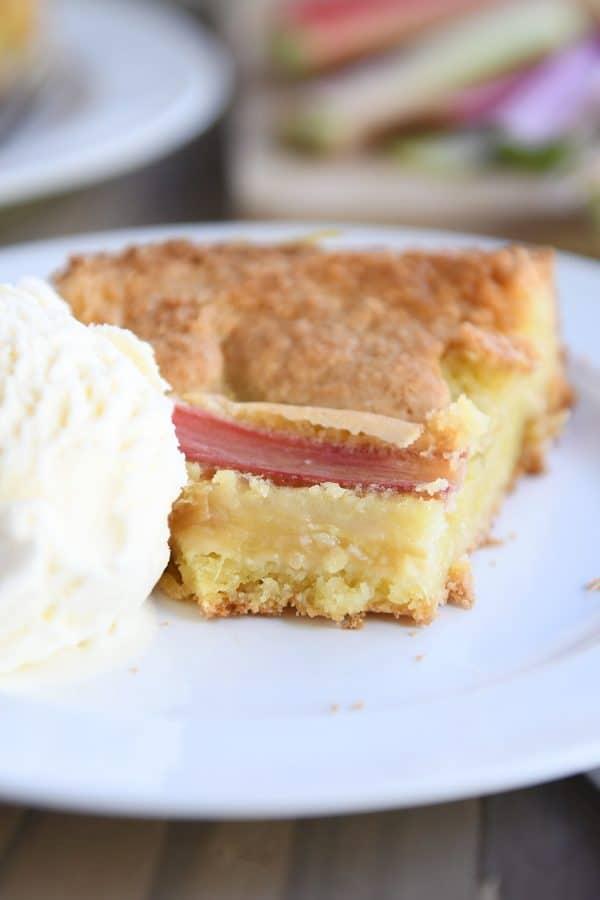 rhubarb custard cake on white plate with ice cream