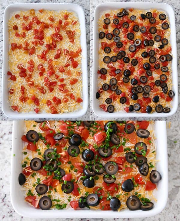 tomatoes, olives and green onions layered on 7-layer dip in white dish