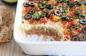 scoop taken out of 7-layer dip in white casserole dish