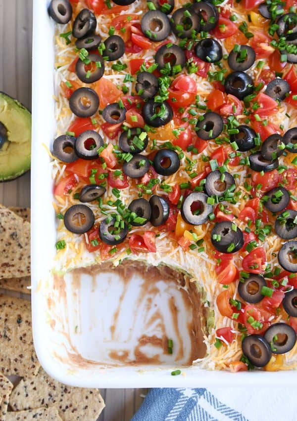 top down view of easy 7-layer dip in white casserole dish