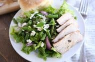 grilled pork salad with pork, red onions, green beans and roll on white plate