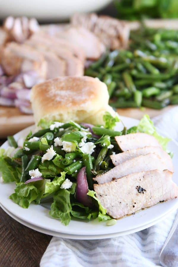 grilled pork salad with sliced pork and roll on white plate