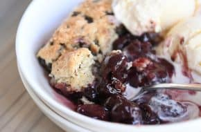 serving of cherry chocolate cobbler with chocolate chunk biscuit and vanilla ice cream in white bowl