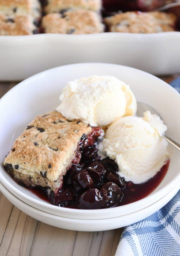 scoop of cherry cobbler with chocolate chunk biscuit in white bowl with vanilla ice cream