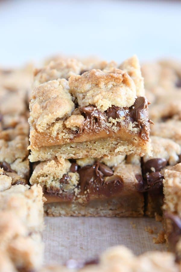 cookie bar cut into square and sitting on top of pan of cut bars