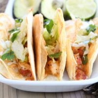 three crispy shrimp tacos in flour tortillas with lettuce on white tray