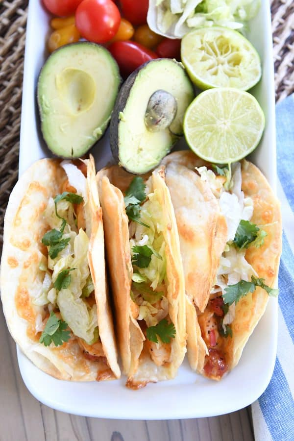 top down view of a tray of shrimp tacos, an avocado cut in half, and a lime cut in half