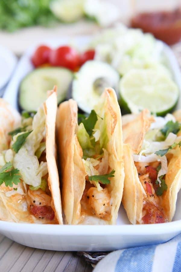three crispy shrimp tacos with lettuce on white tray