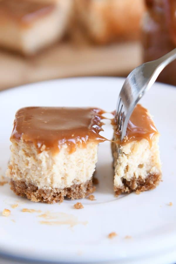 cutting off bite of dulce de leche cheesecake square with fork on white plate