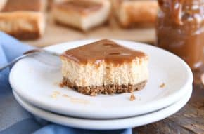 dulce de leche cheesecake square on white plate with bite taken out
