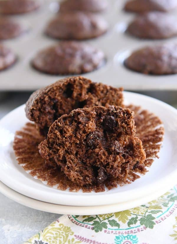 double chocolate zucchini muffin in half on muffin liner