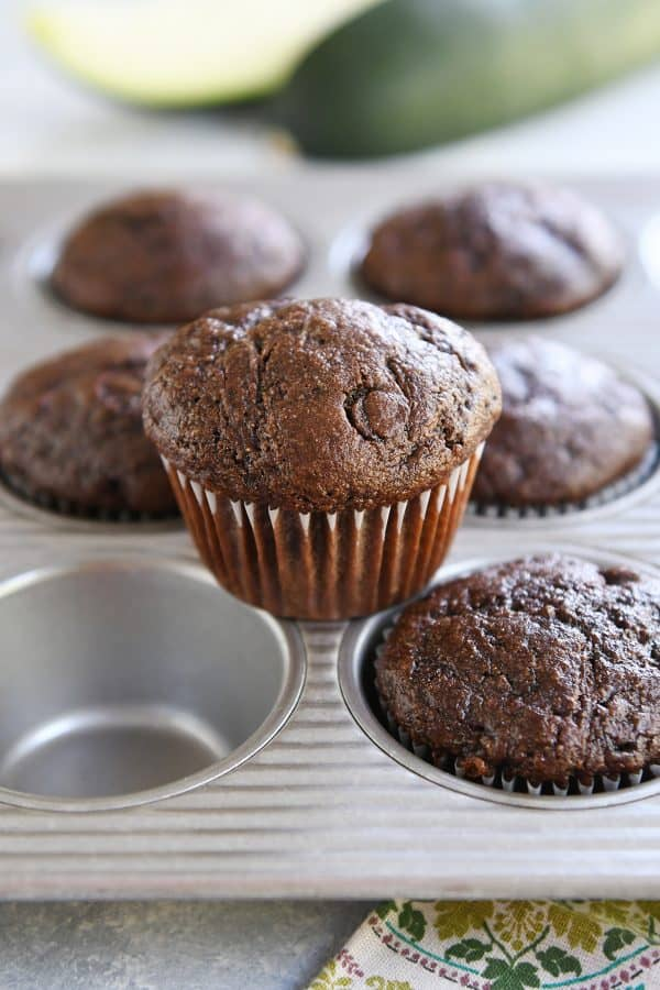baked chocolate zucchini muffin sitting on top of muffin tin pan