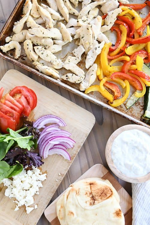 A sheet pan with cooked chicken and pepper slices next to a cutting board with sliced vegetables.