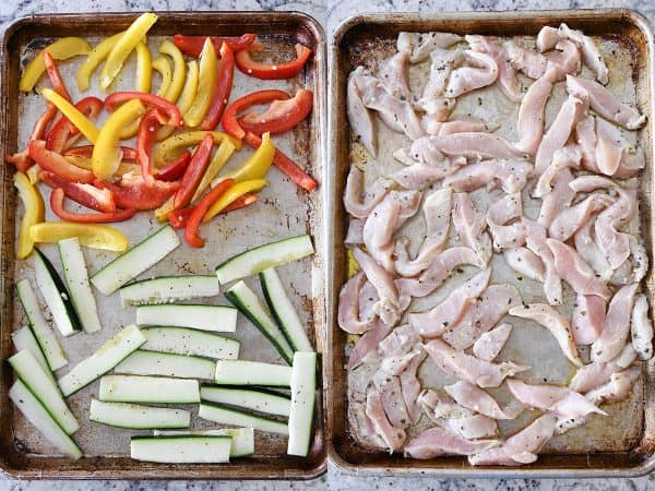 zucchini and bell peppers and marinated chicken on sheet pans