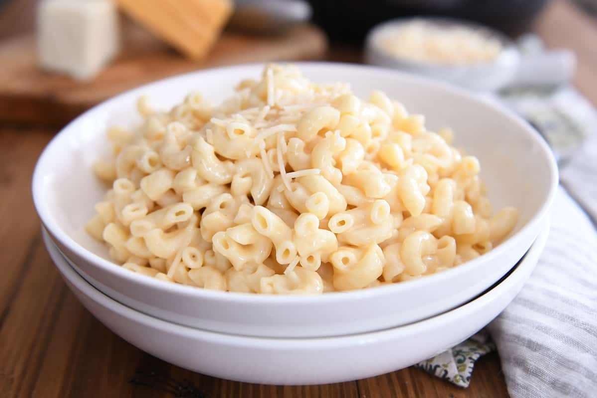 mac and cheese in white bowl with Parmesan sprinkled on top