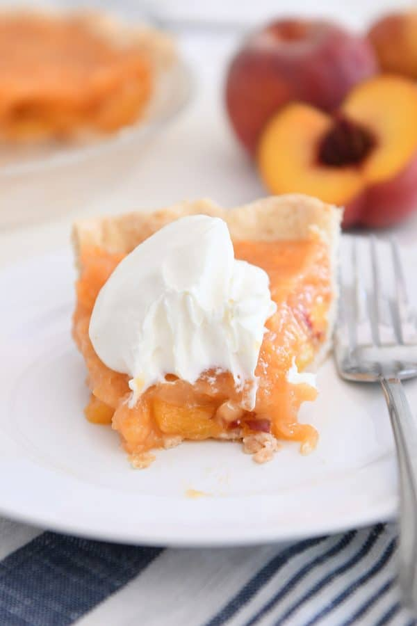 slice of fresh peach pie on white plate with bite taken out