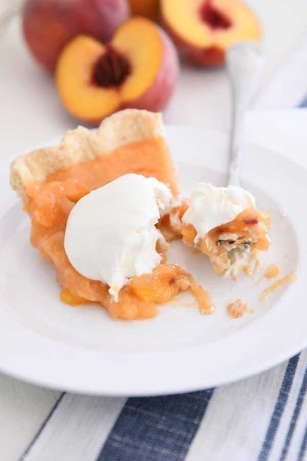 bite of fresh peach pie on fork on white plate