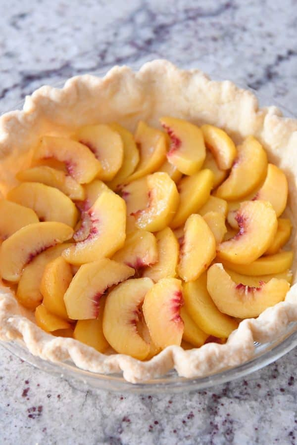 baked pie shell with sliced fresh peaches evenly placed on the bottom