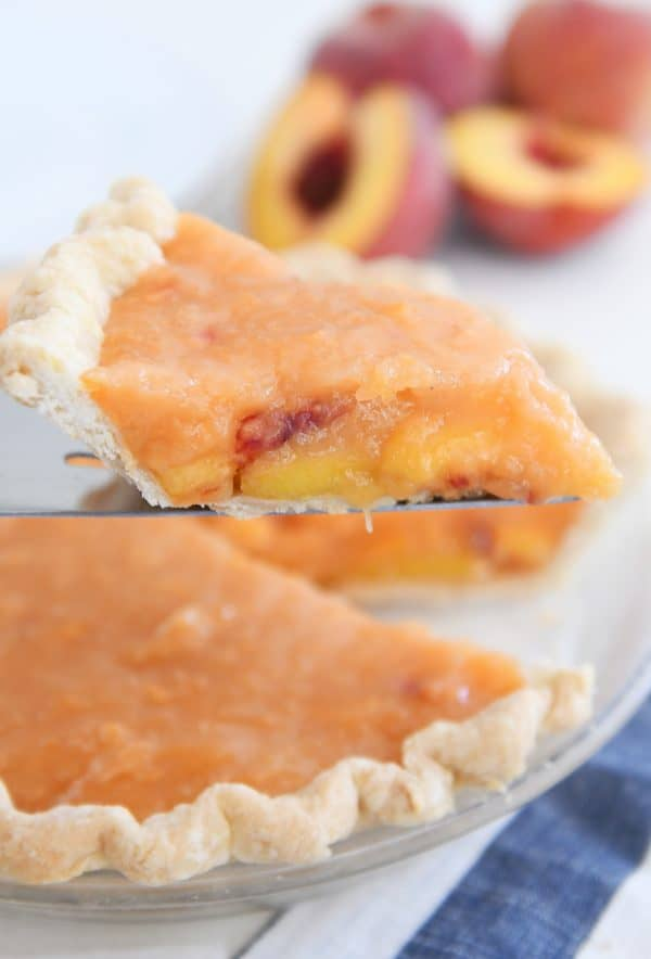slice of fresh peach pie on pie server
