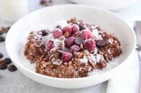 double chocolate steel cut oats in white bowl with coconut, chocolate chips and raspberries