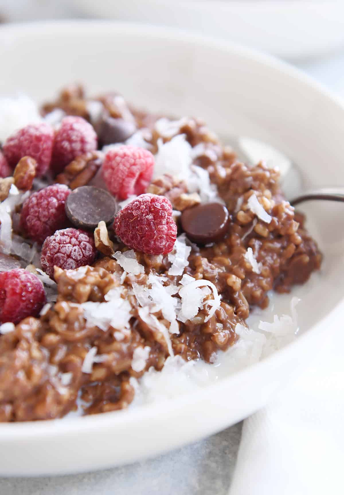 instant pot chocolate steel cut oats in white bowl with chocolate chips and frozen raspberries