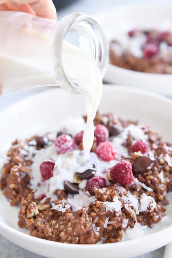 pouring milk over instant pot chocolate steel cut oats in white bowl with frozen raspberries