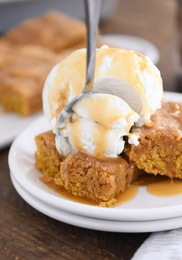 fork taking bite out of easy pumpkin snickerdoodle bar with vanilla ice cream and butterscotch sauce on white plate