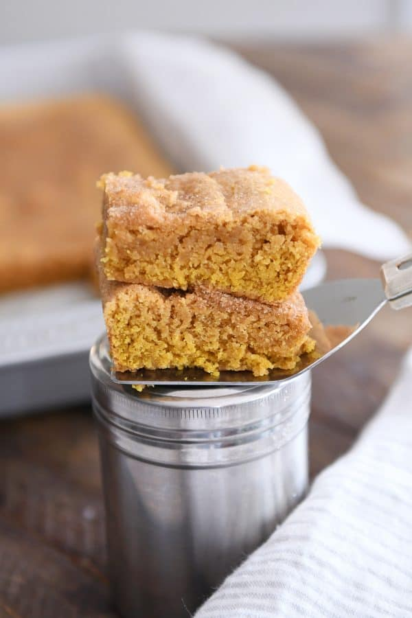 two pumpkin snickerdoodle bars stacked on top of cinnamon and sugar canister