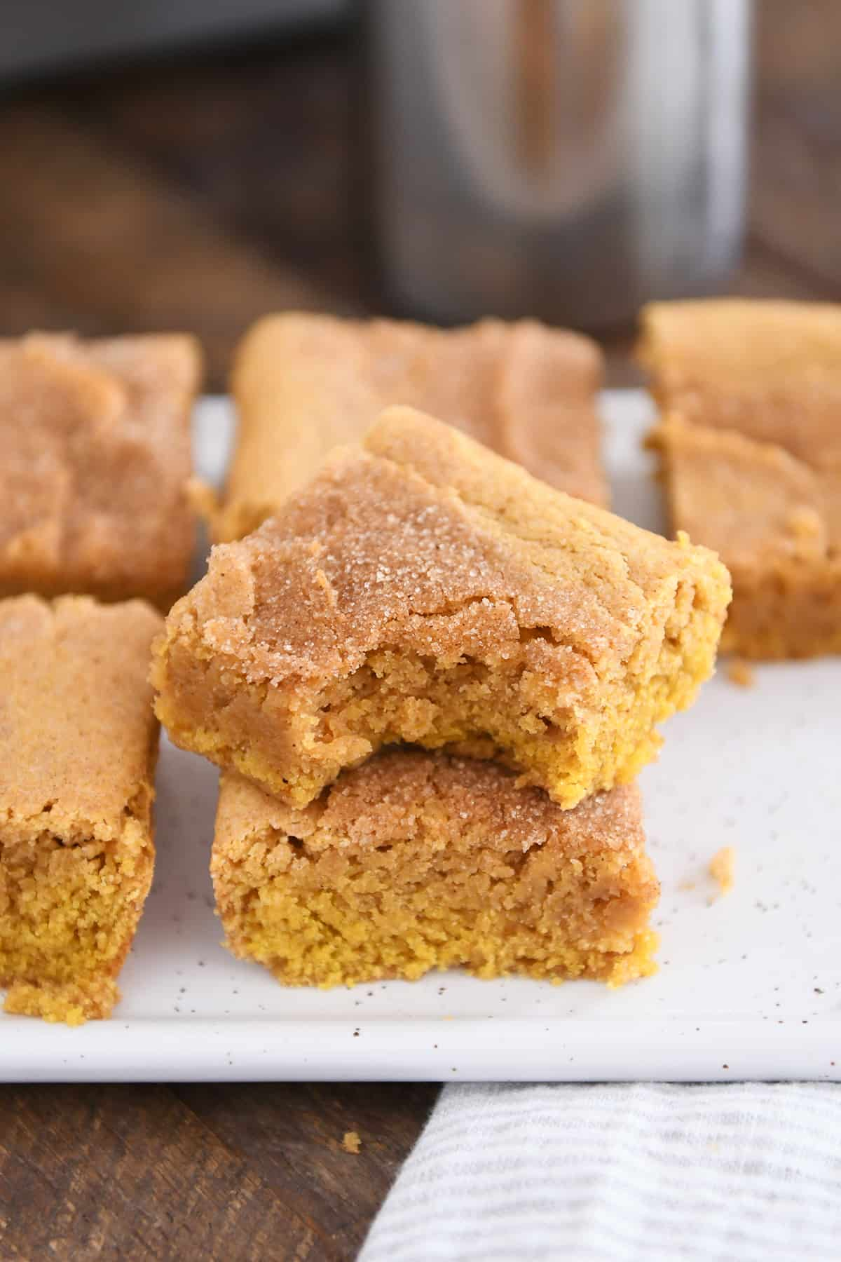 two pumpkin snickerdoodle bars stacked on white tray with bite taken out of top bar