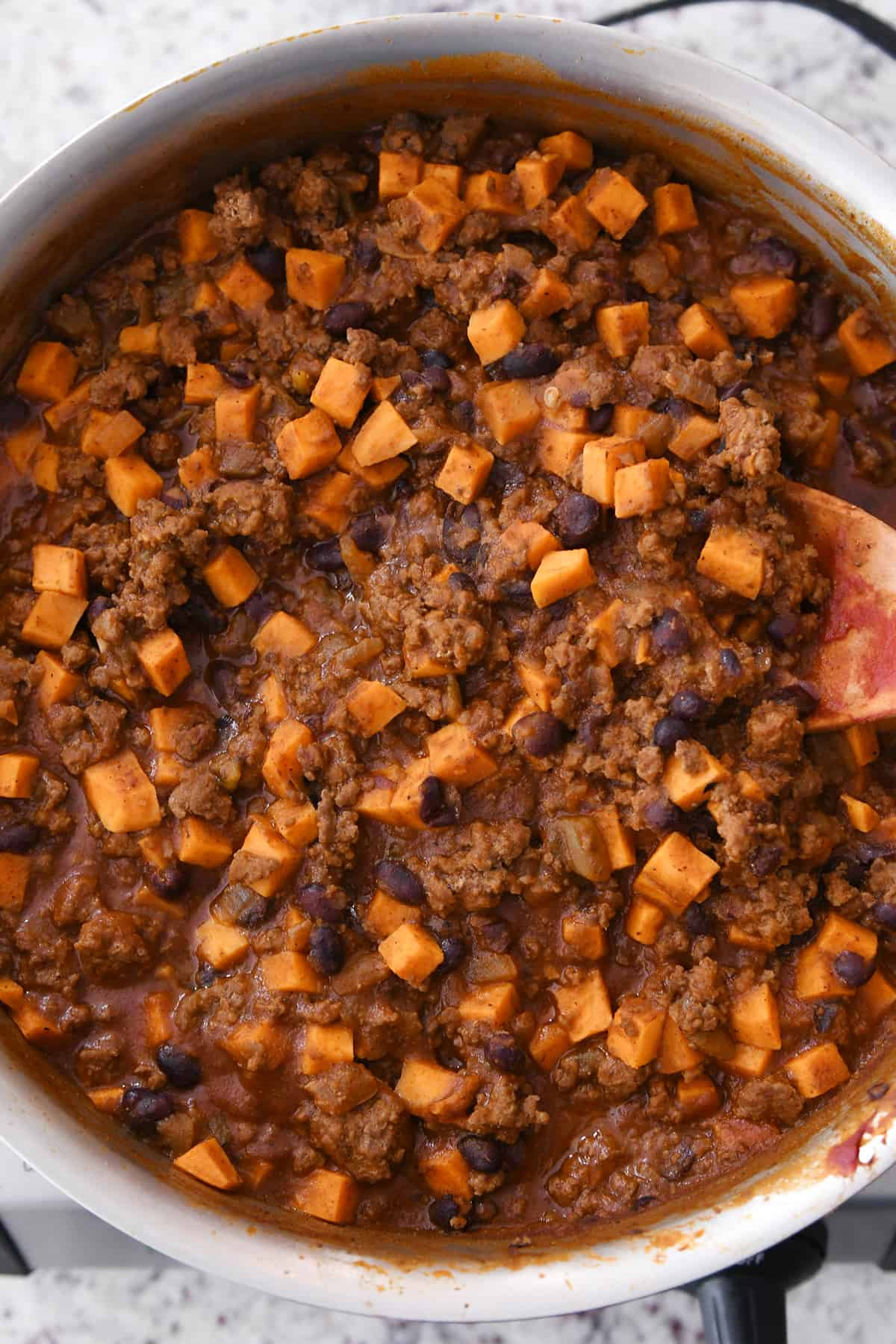 wooden spoon in skillet with sweet potato black bean burrito filling