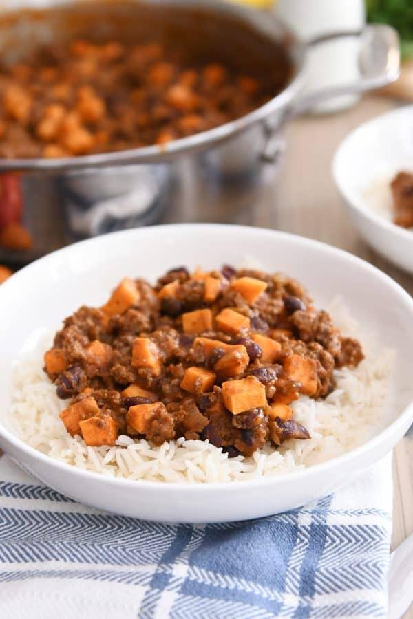 white bowl with rice and sweet potato black bean burrito filling