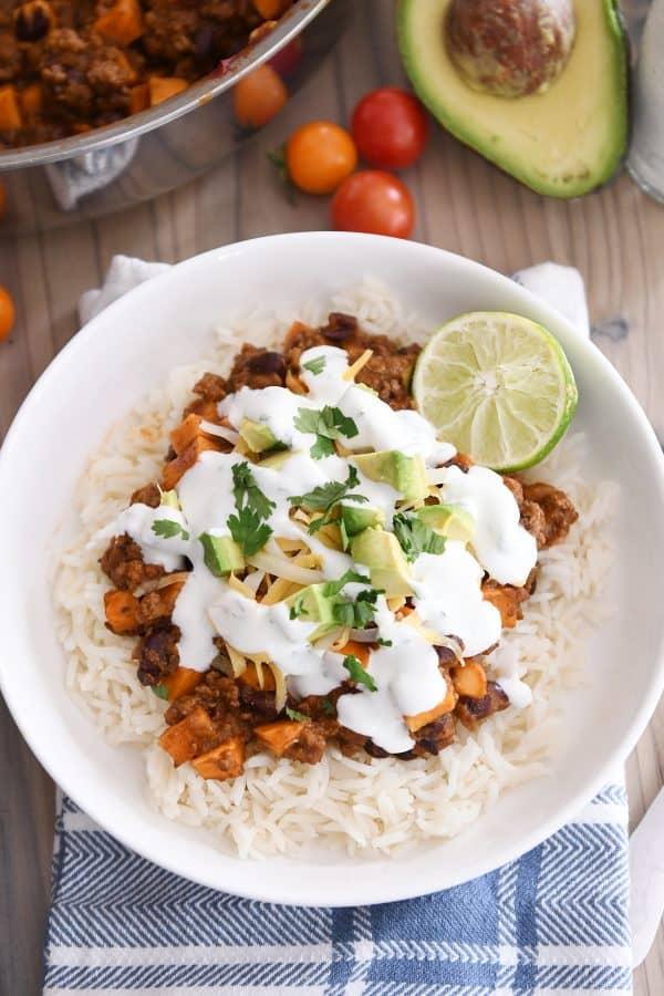 white rice topped with sweet potato black bean burrito ingredients, avocados, cilantro and limes