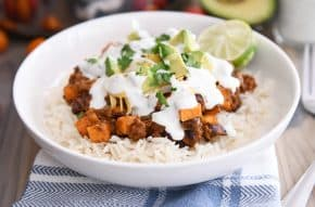 white rice topped with sweet potato black bean burrito ingredients, avocados, cilantro and limes