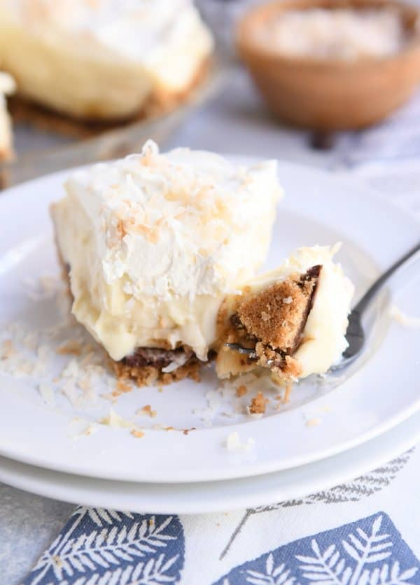 bite of banana coconut cream pie on fork on two white stacked plates