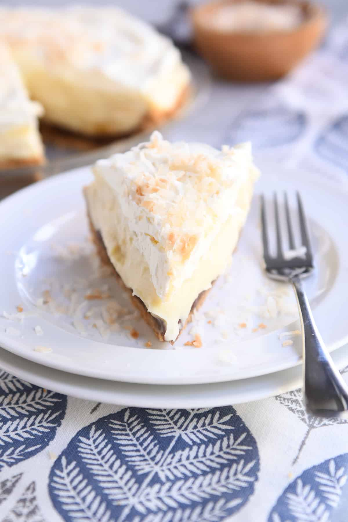 slice of banana coconut cream pie on two white stacked plates