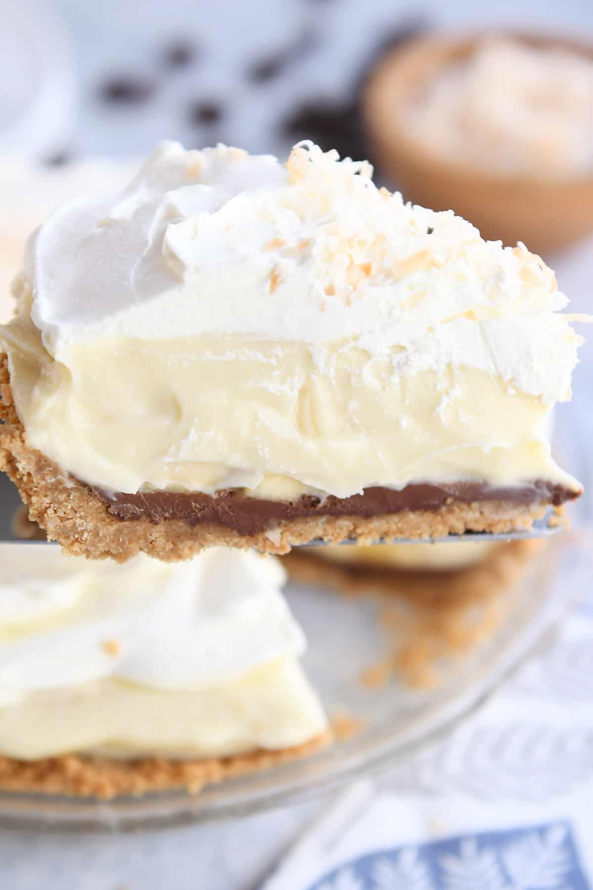 piece of banana coconut cream pie on pie server