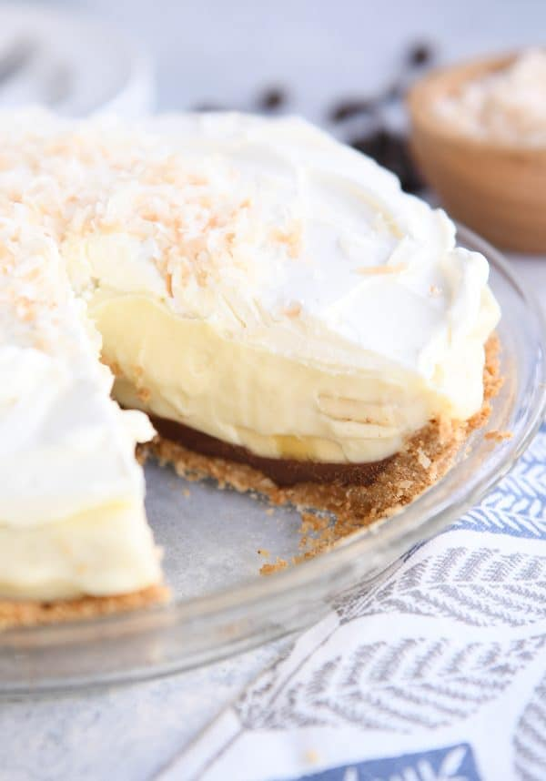 whole banana coconut cream pie in glass pie plate with piece removed