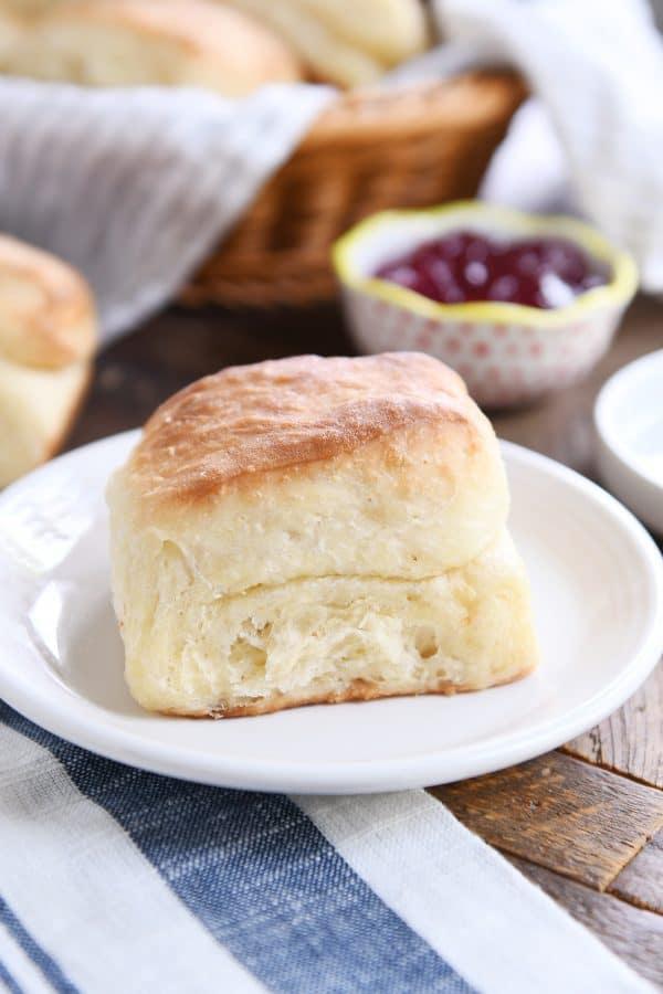 super fluffy dinner roll on white plate on white and blue napkin