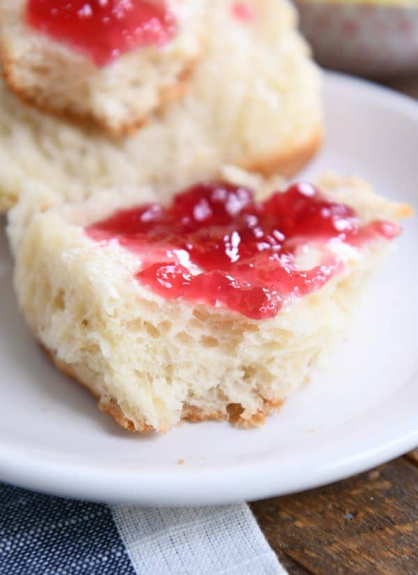 close up view of super fluffy dinner roll with butter and jam on white plate