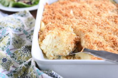 metal spoon scooping out spoonful of baked mashed potatoes with parmesan topping in white dish